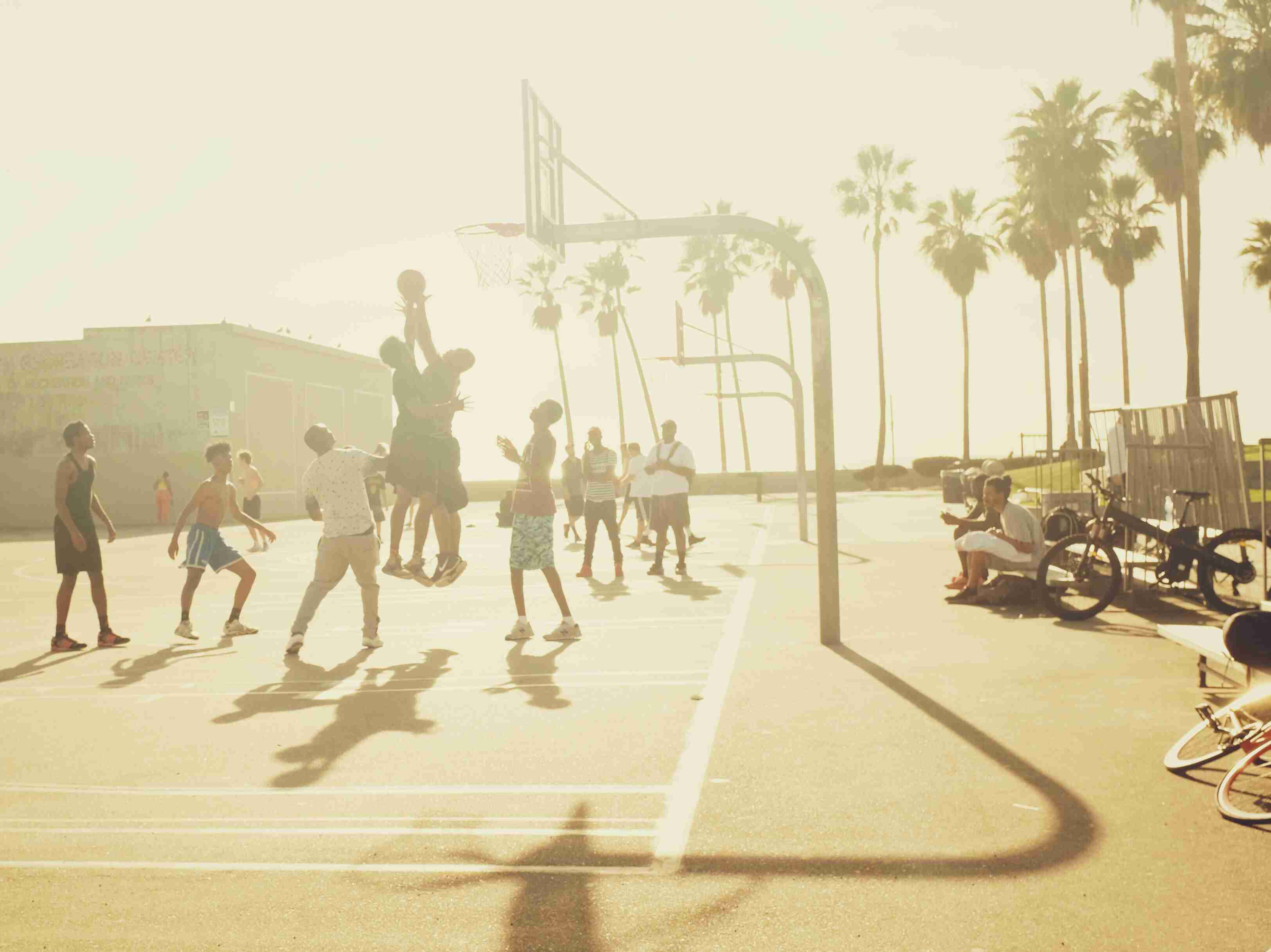 Group Of People Playing Basketball In Venice Beach, United States During Sunset