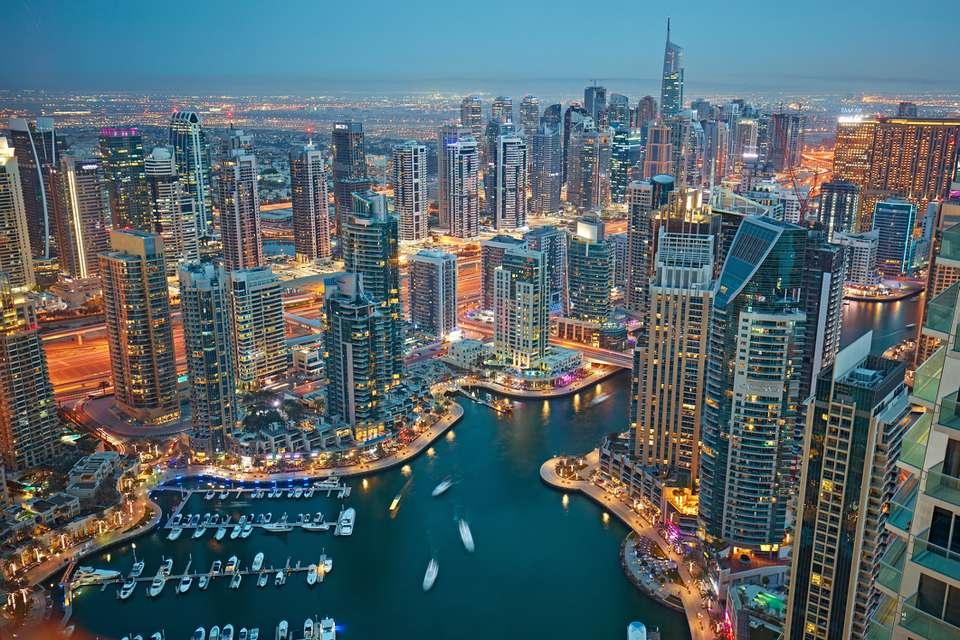 Aerial view of skyscrapers around the Dubai marina at dusk