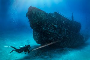 Full Length Of Woman Diving Underwater By Shipwreck