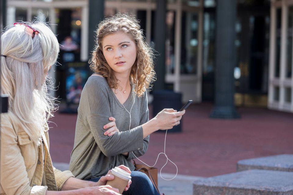 Teenage girl rolling her eyes while wearing earphones.