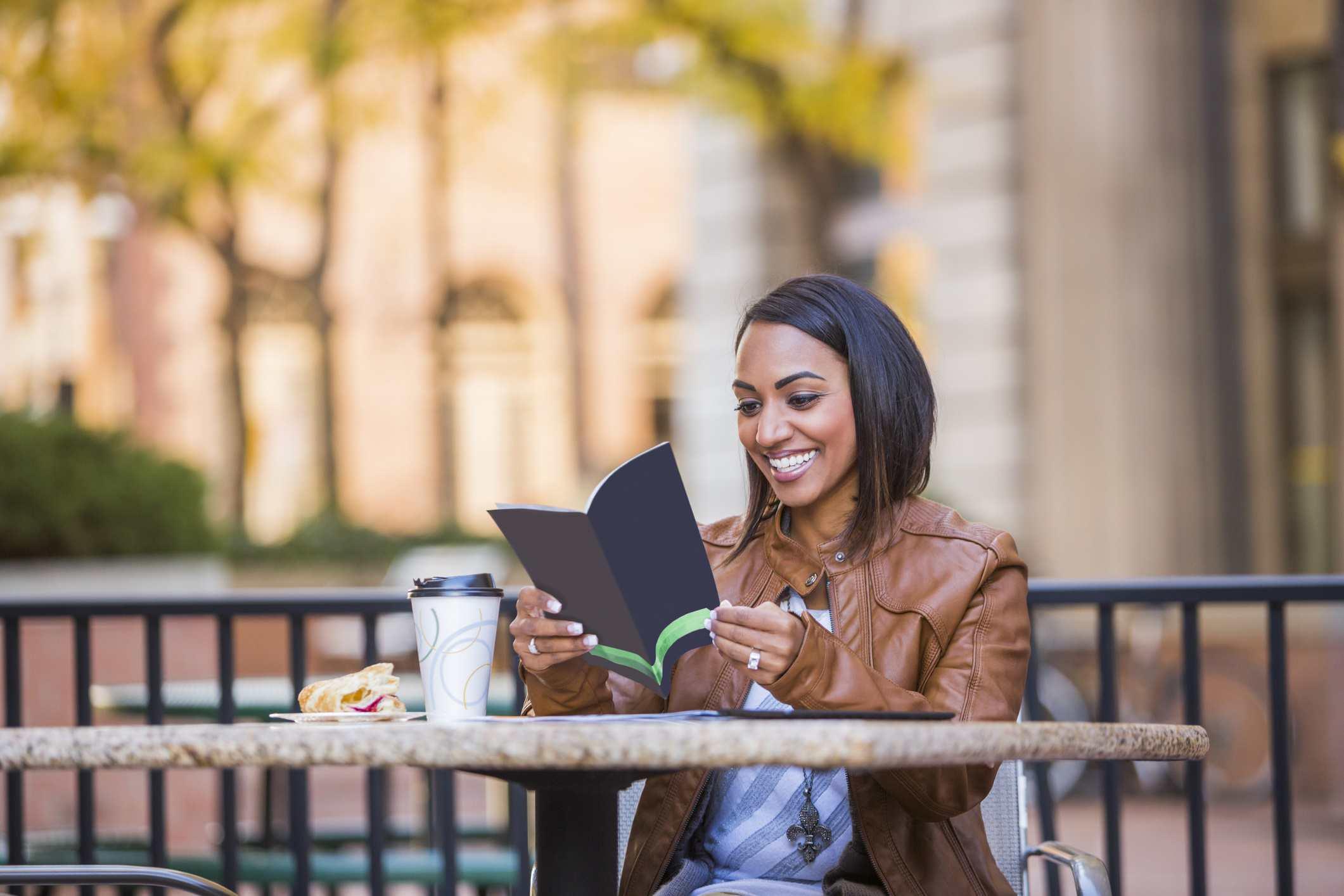 Mujer leyendo el folleto en el café al aire libre