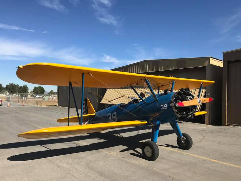 blue biplane with yellow wings on a runway