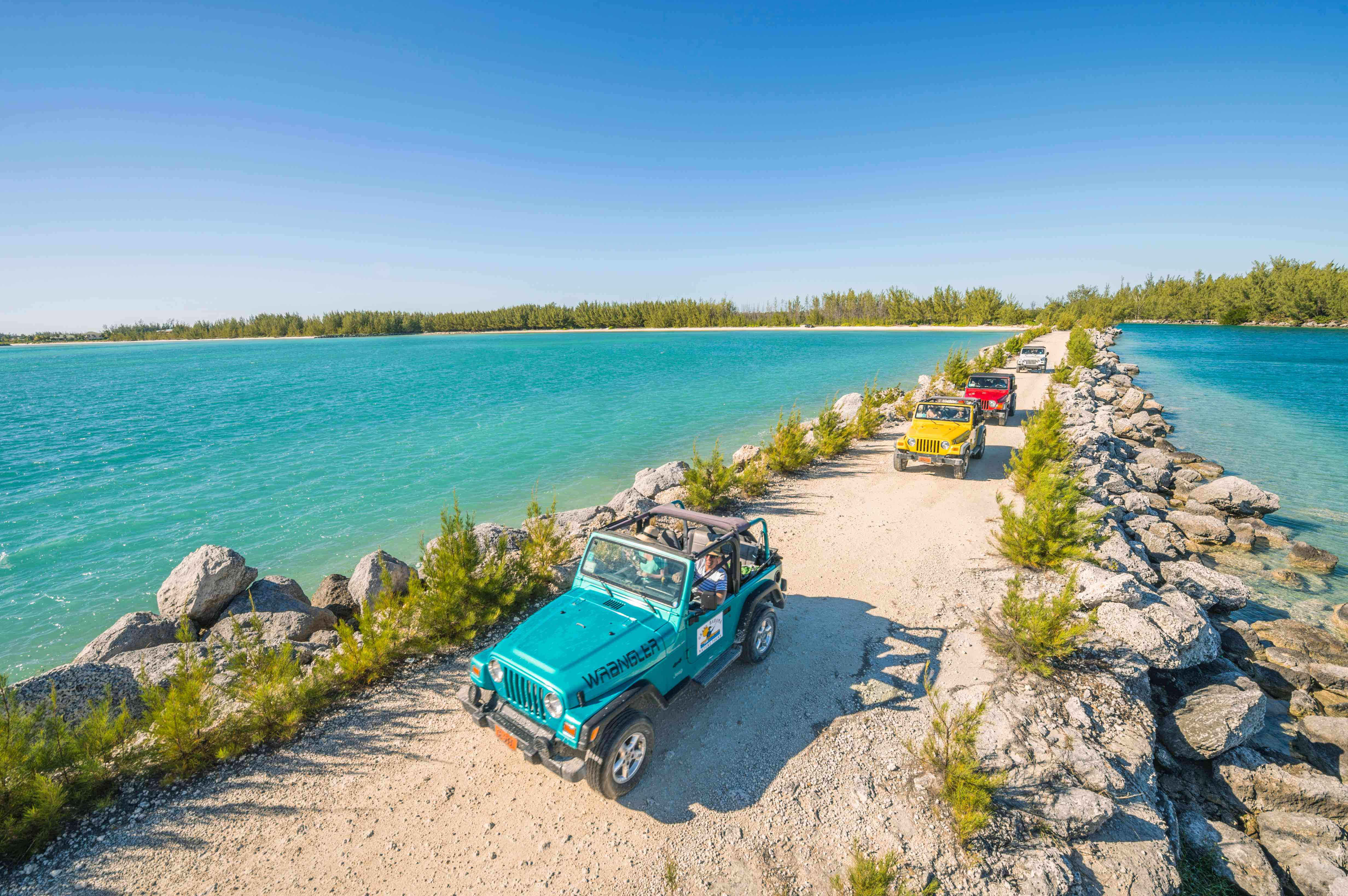 Colorful jeeps driving along a sandy road with water on both sides on Freeport, the Bahamas