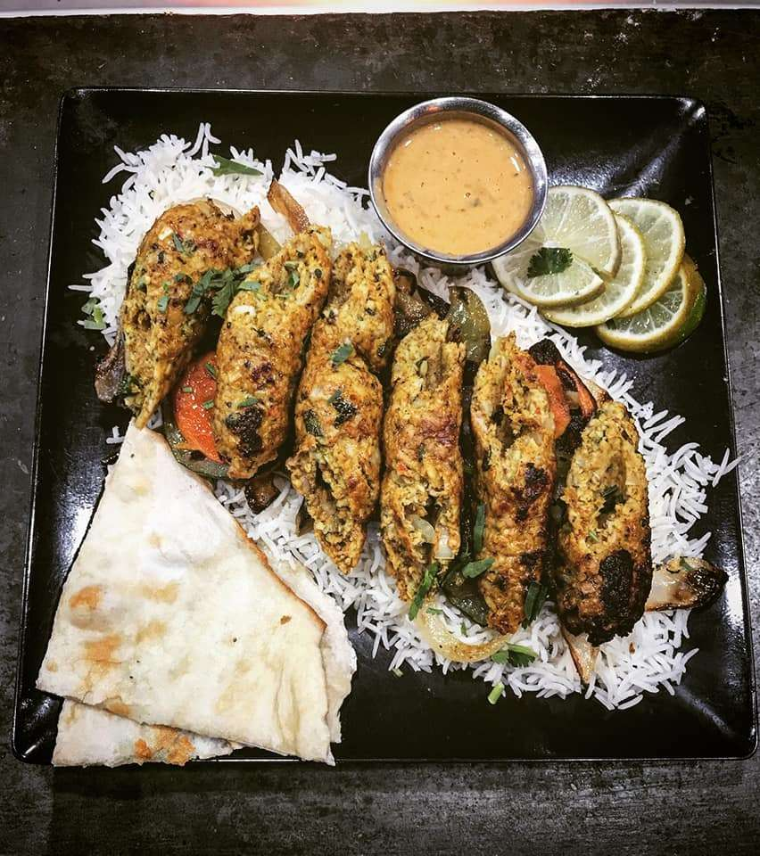 Overhead shot of naan, rice and kebabs from Stone Hearth Indian Cafe