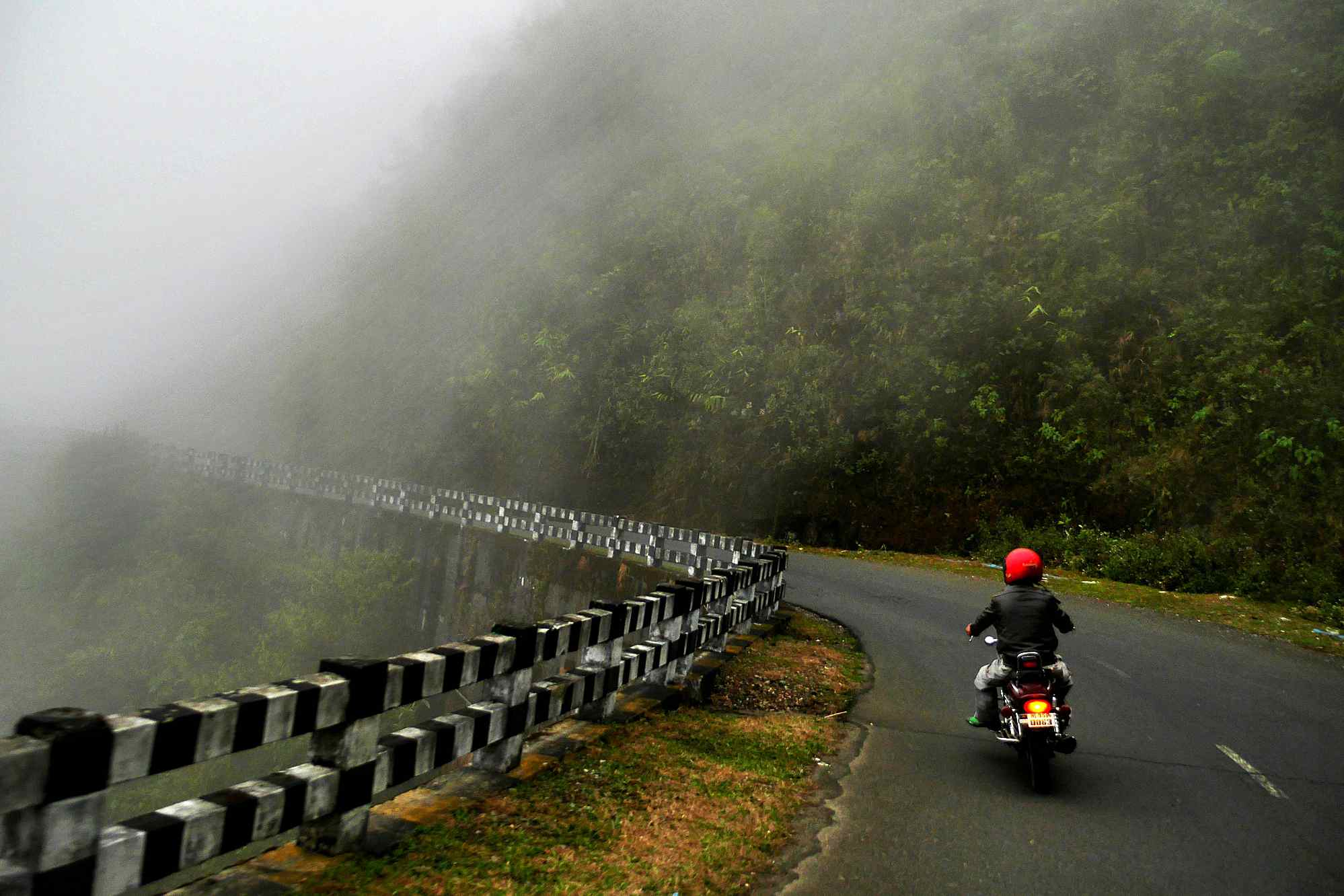 A motorbike rider turning into thick fog in the mountains of Meghalaya.