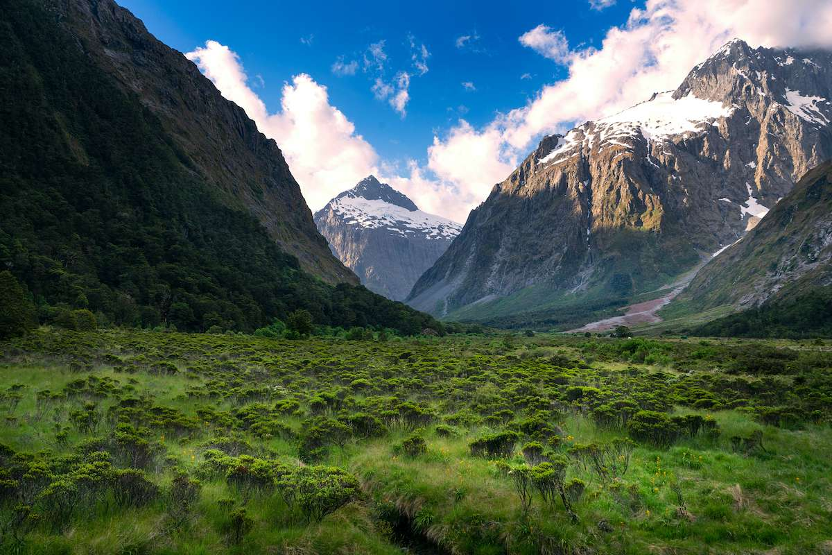 A glacier-carved valley with snowcapped peaks lining the walls.