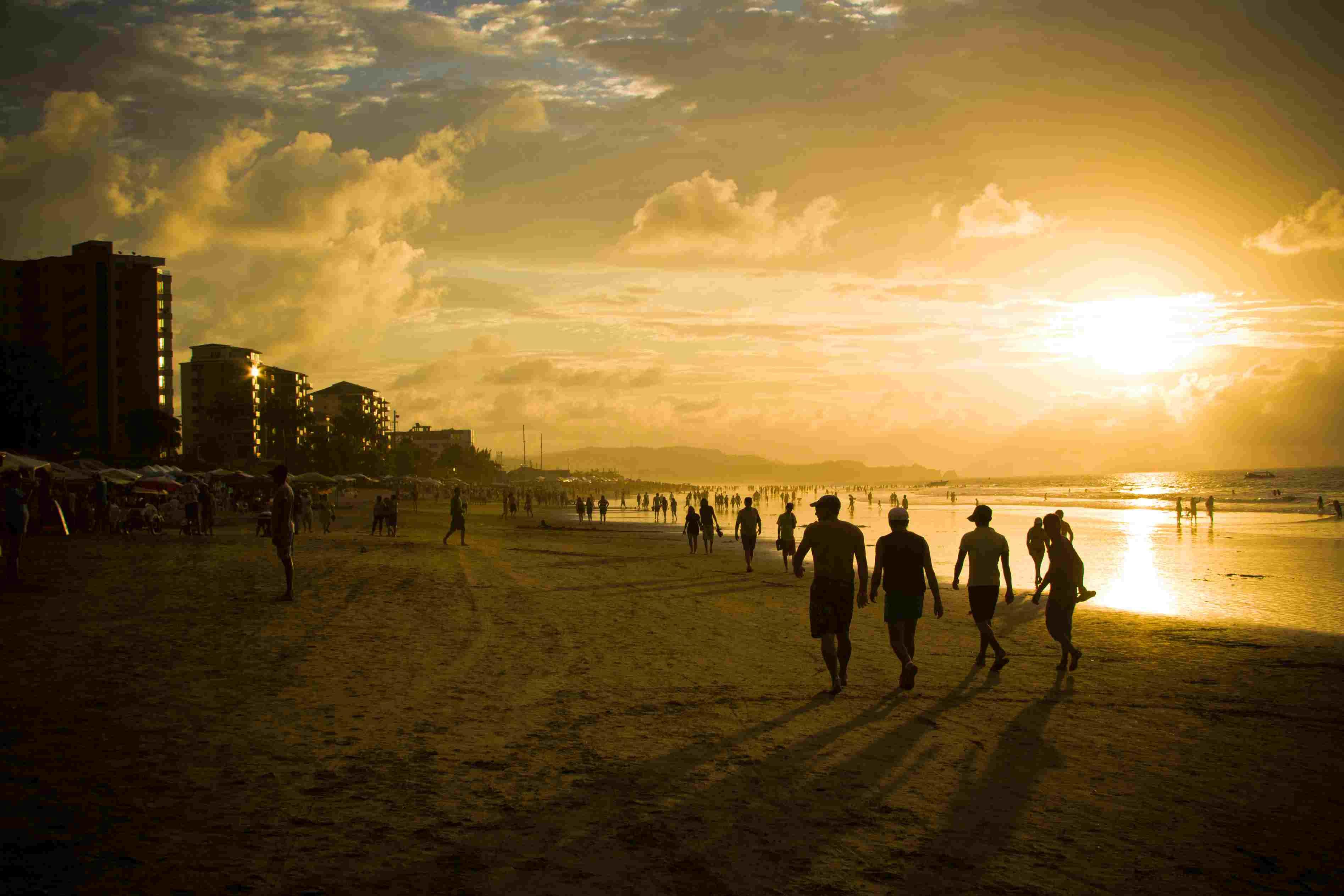 People walking along Tonsupa Beach in Esmeraldas, Ecuador