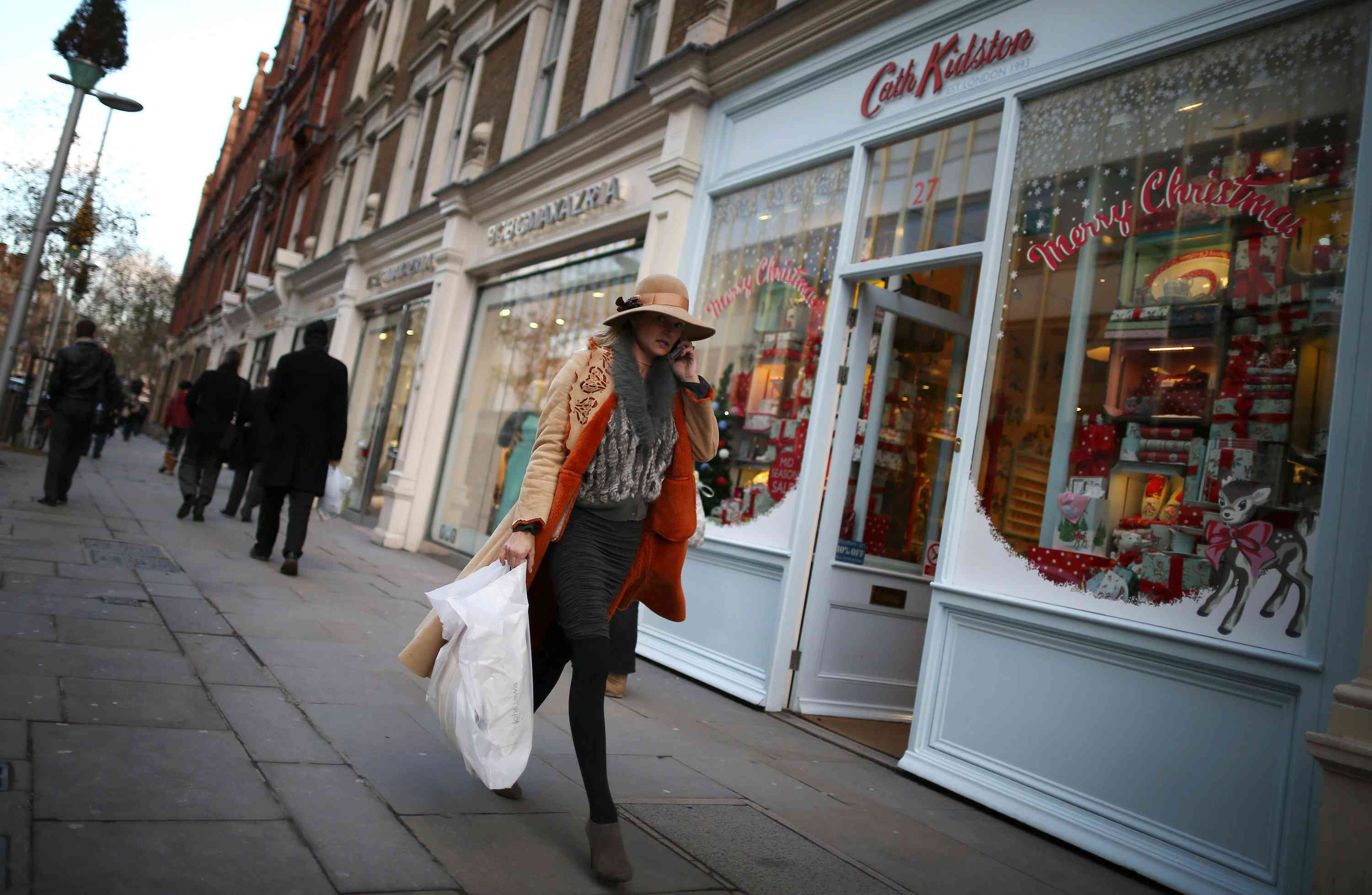 Woman holding a phone, walking down a street in London with shopping bags