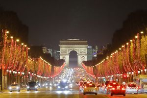 Paris, 8th arrondissement. Champs Elysees Avenue at night and Arc de Triomphe. Christmas illuminations 2018. Cars on the avenue.