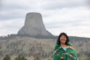 An Indigenous woman wrapped in a blanket smiling in front of Devil's Tower in Wyoming