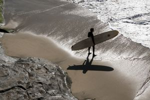 Surfer heading out to surf at Capitola California USA