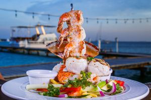 A decadent shrimp dish from Pinchos with a view of the pier and sea in the background