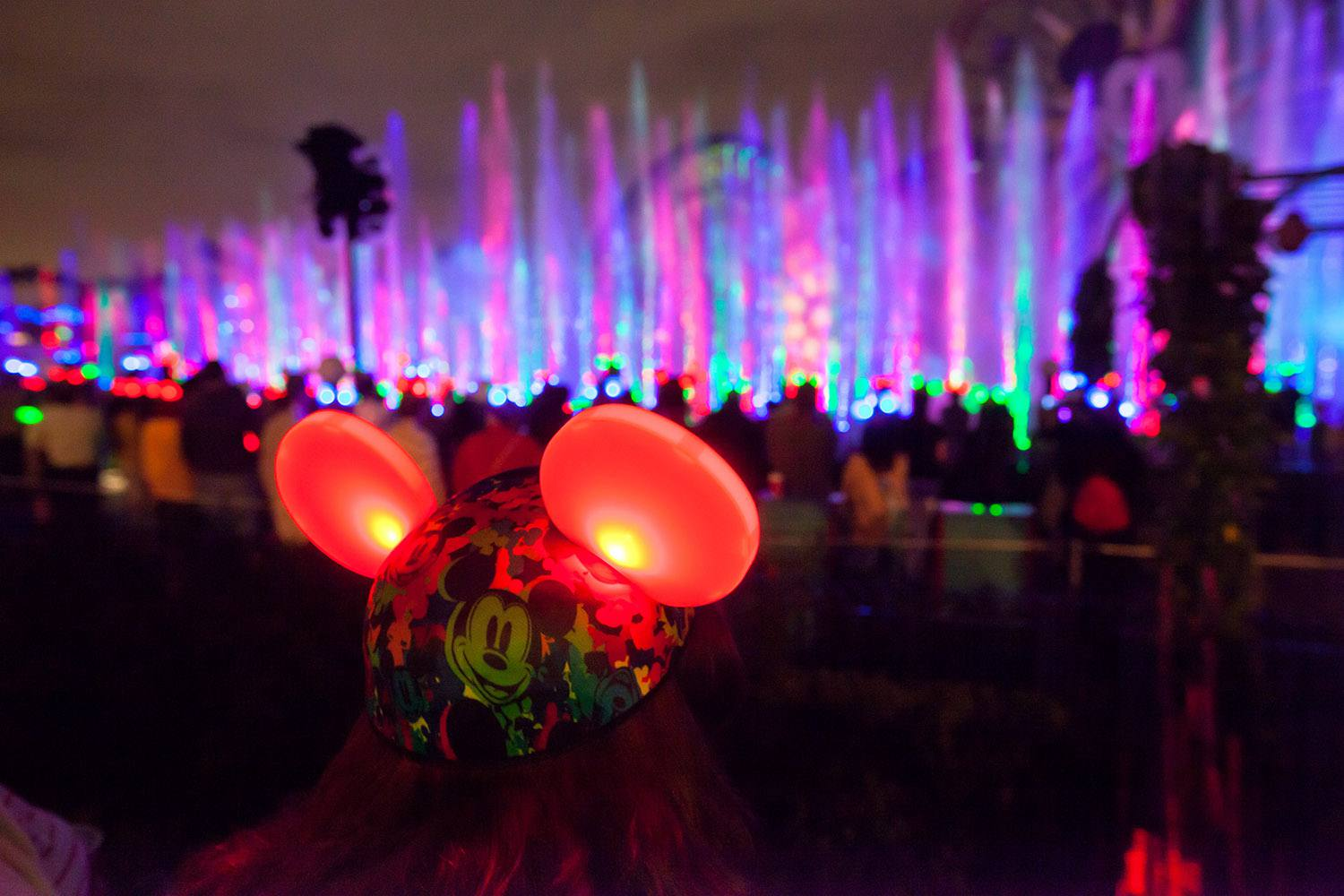 a woman's mouse ears glow as she watches World of Color