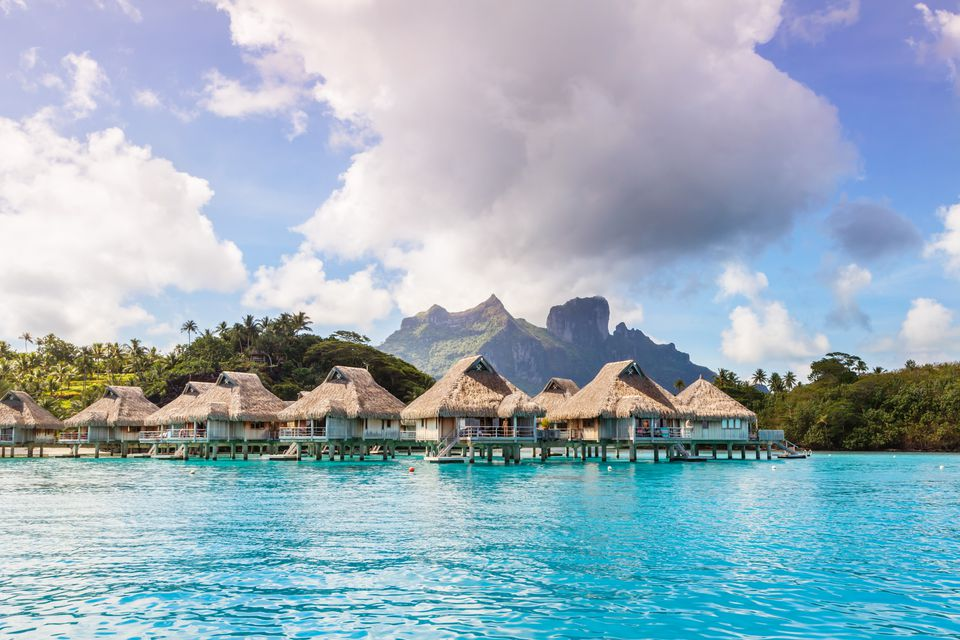Overwater bungalows in the lagoon of Bora Bora with mountains in the background