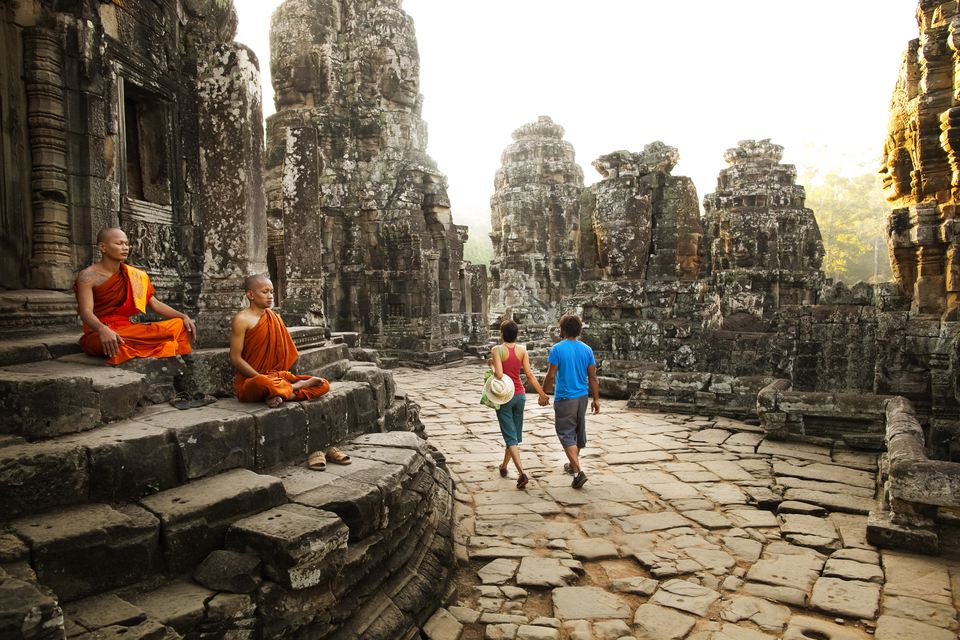Couple visiting Buddhist temple, Angkor, Siem Reap, Cambodia