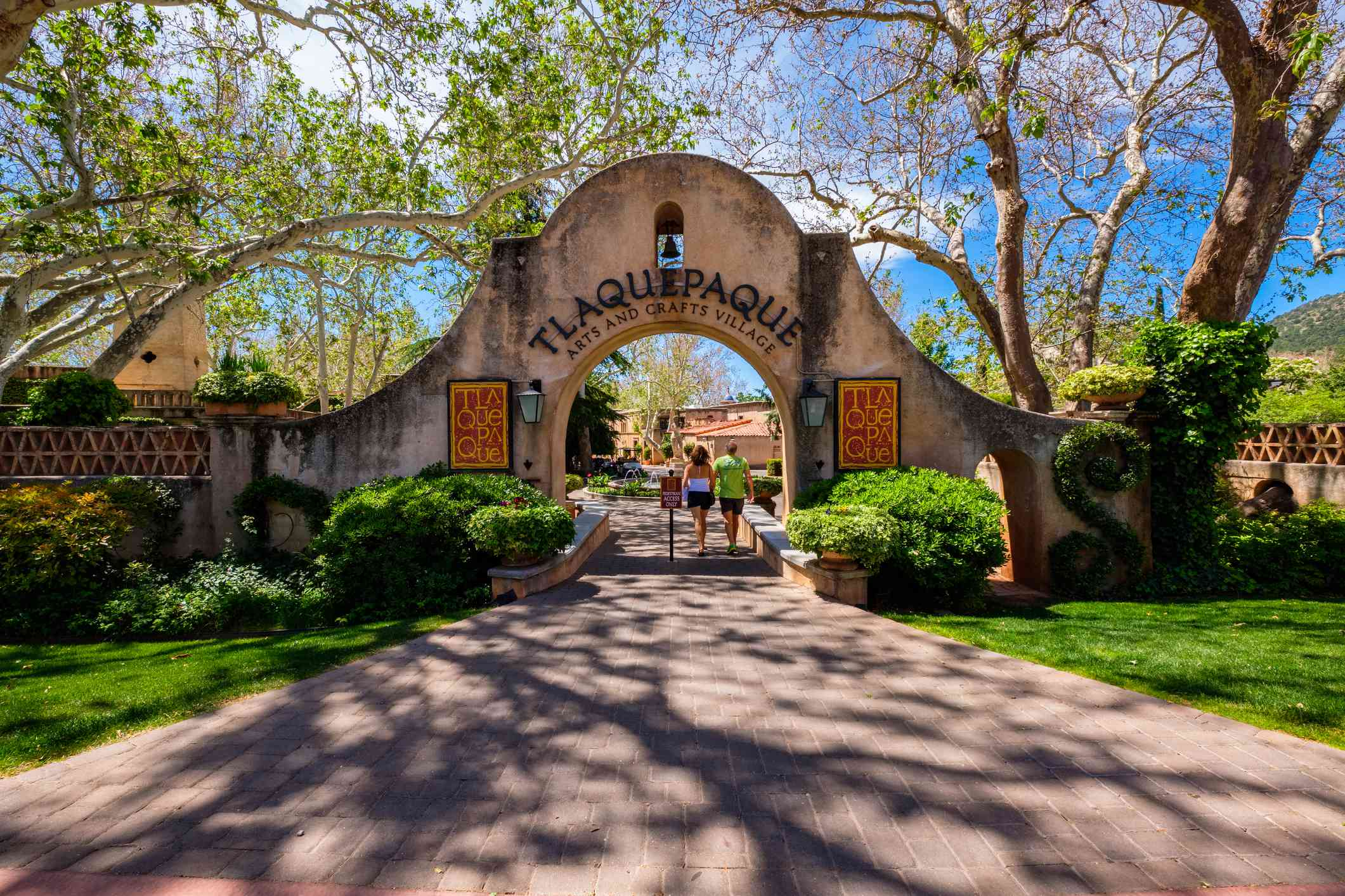Two people walking under the entrance arch to Tlaquepaque Village Sedona