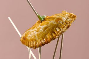 Fried hand pie on a skewer with five wooden skewers supporting it on a pinkish-beige background