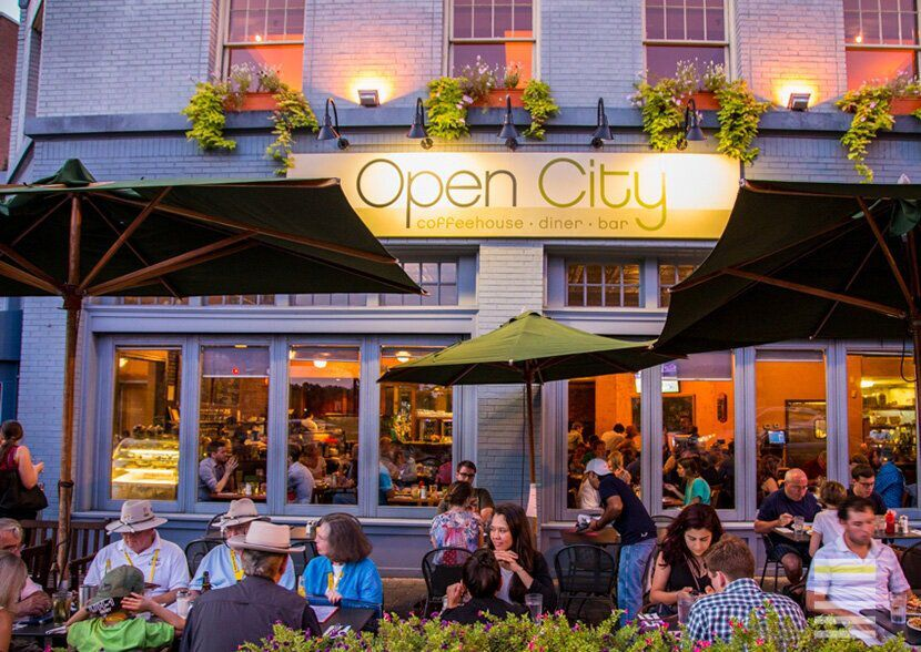 People eating on the outdoor patio at Open City restaurant at dusk