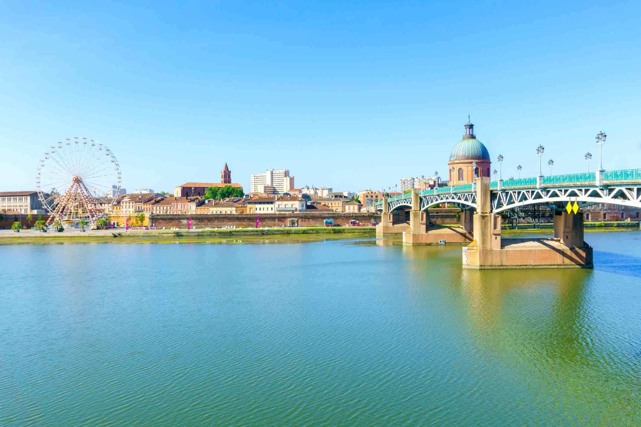 The Saint-Pierre bridge and Ferris Wheel and Hospital De La Grave in Toulouse, France