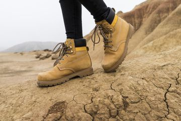 Spain, Navarra, Bardenas Reales, hiking shoes of young woman in nature park, close-up