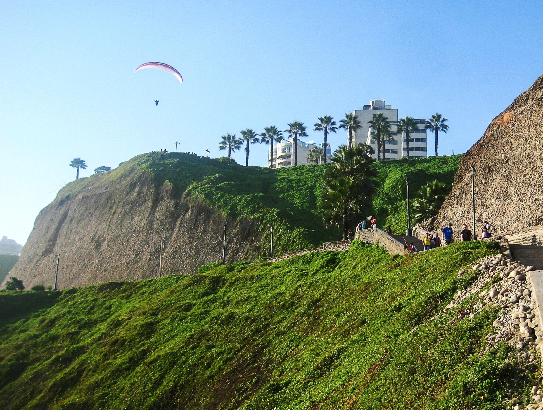 Una persona en parapente sobre las colinas de Lima