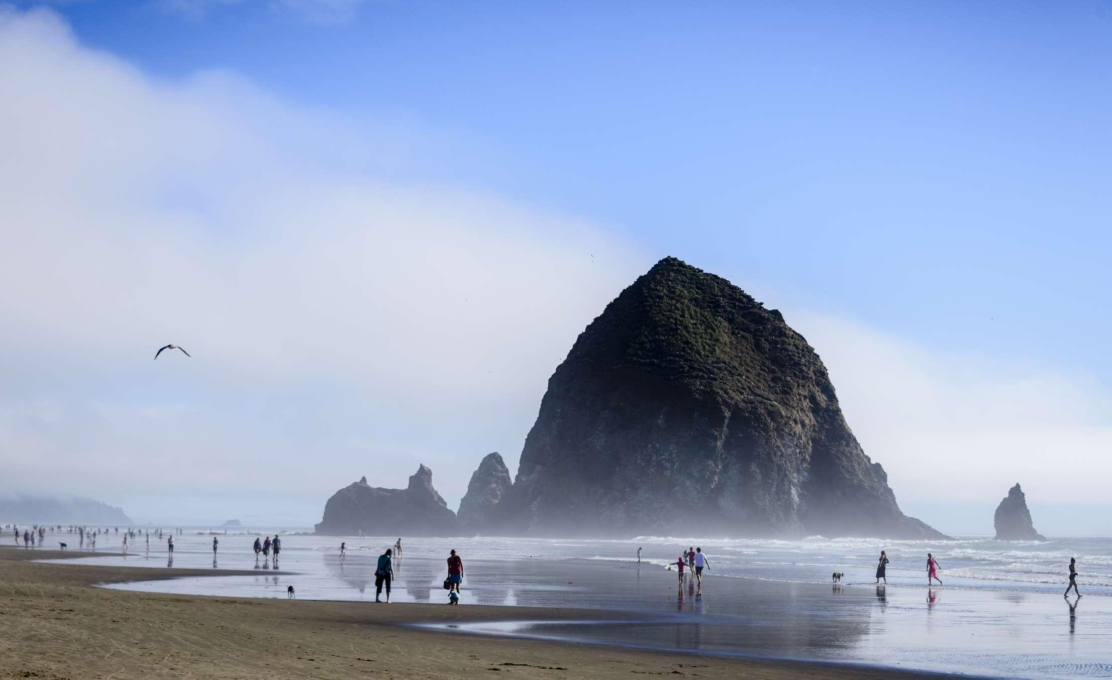 Gente disfrutando de un día en Cannon Beach, Oregon. La formación conocida como Haystack Rock se puede ver en el fondo