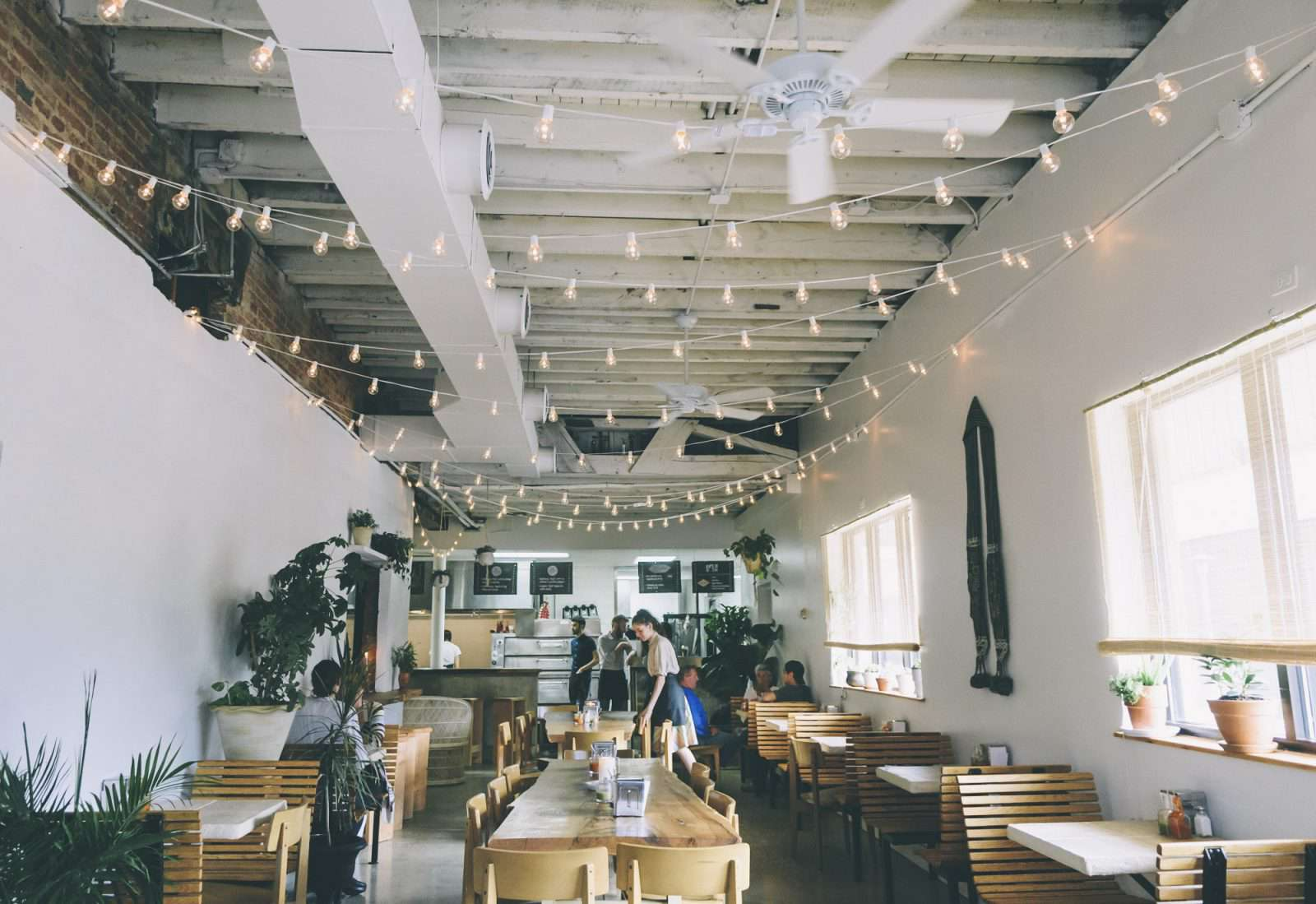 restaurant with white walls, light wooden chairs and high industrial ceilings. There arre strings of lights hanging overhead