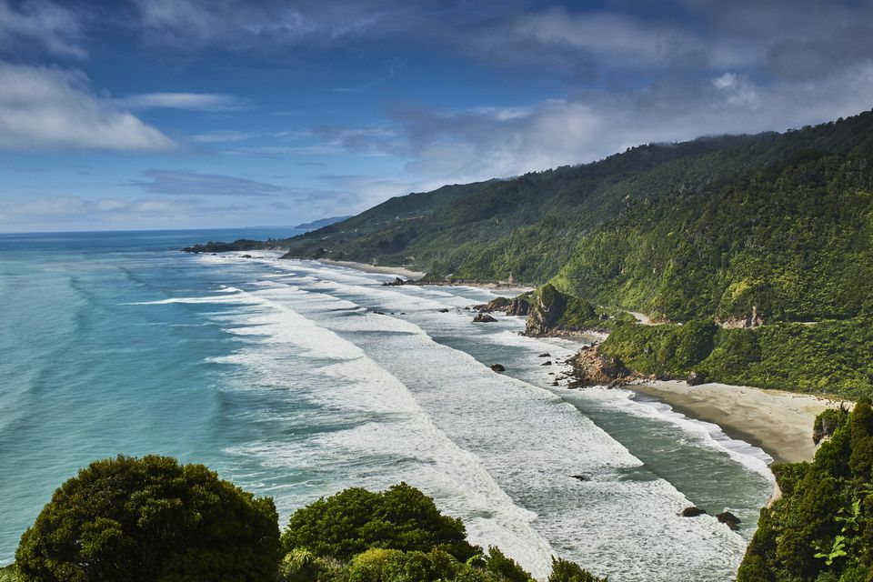 waves breaking on a beach with cliffs covered in rainforest