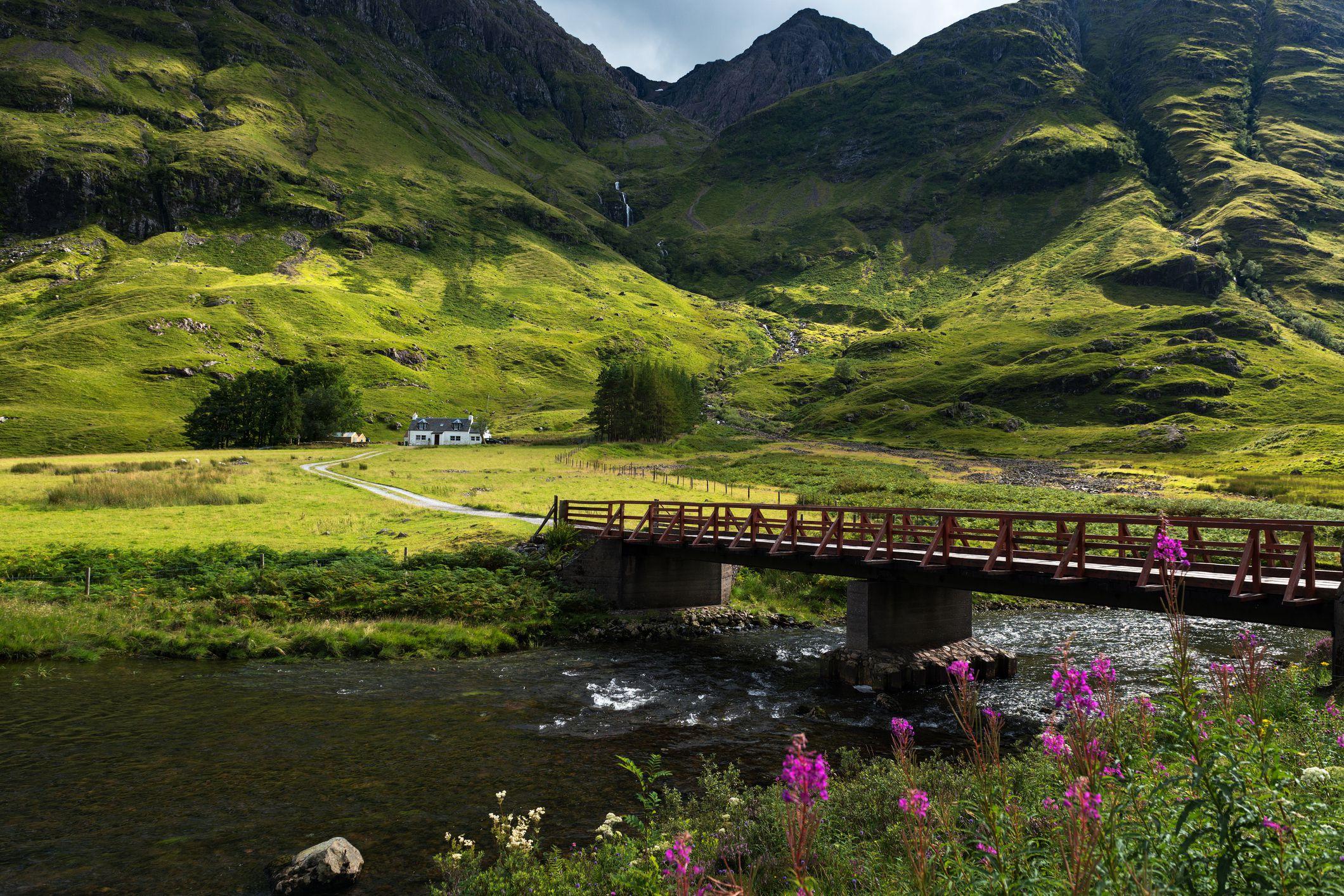 Bridge crossing the river Coe to cottage at Glencoe Highlands , Scotland