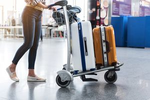 Woman carrying suitcases across hall of airport