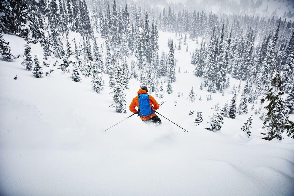 Hombre esquiando a pesar de la nieve fresca durante un recorrido de esquí de travesía