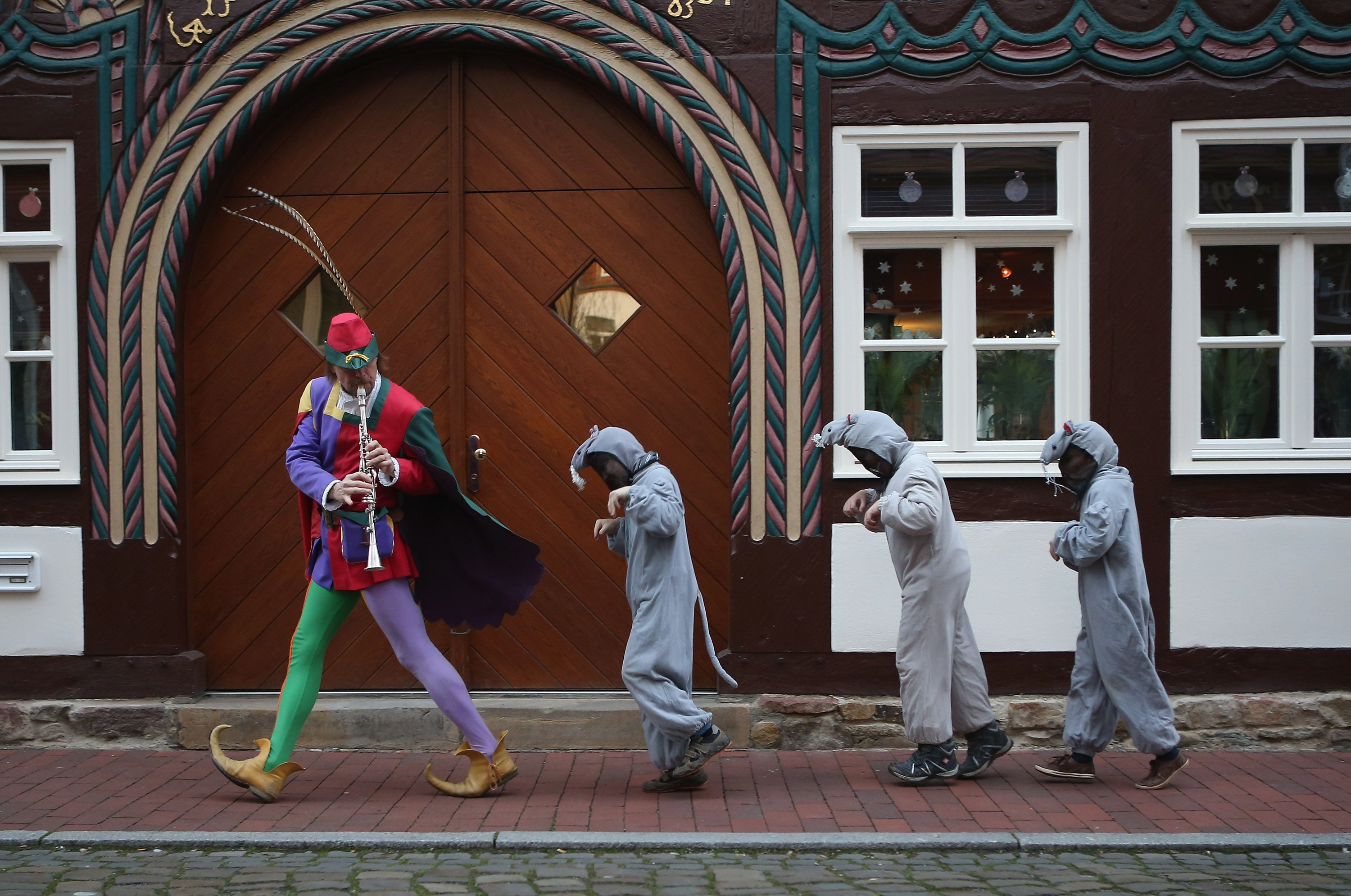 The Pied Piper of Hamelin, actually city tourism employee Michael Boyer, leads local children dressed as rats through a quiet street on November 19, 2012 in Hameln, Germany.