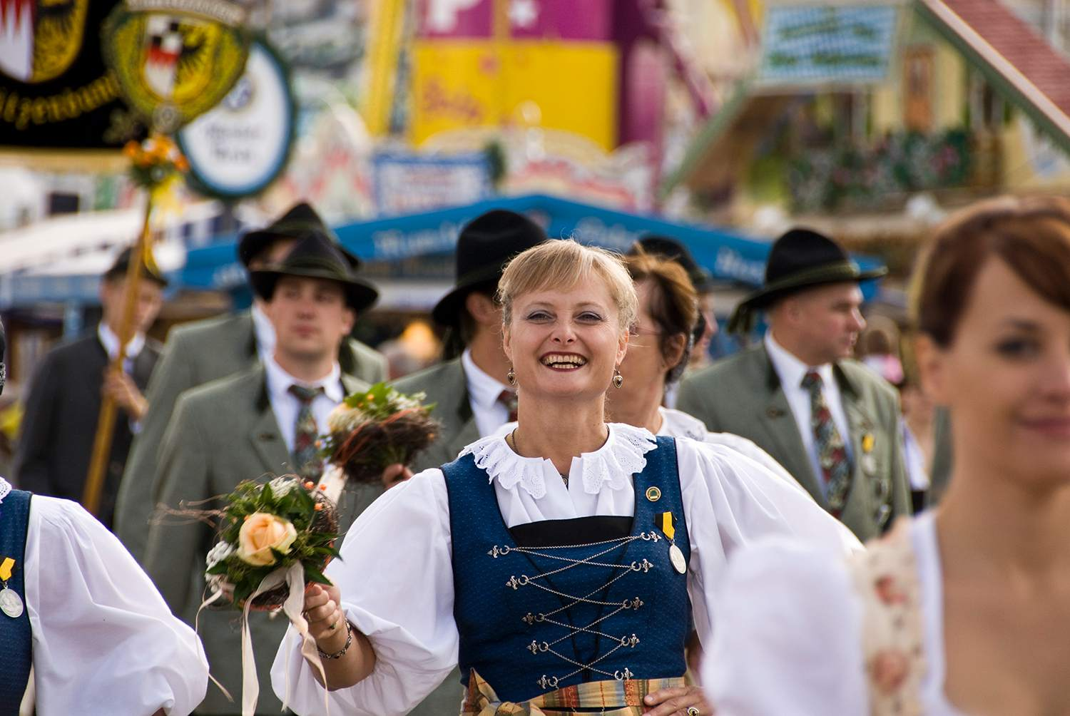 Girls in traditional Bavarian dress marching in Oktoberfest parade.