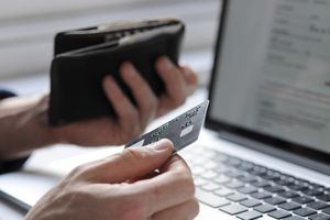 A hand holding a credit card in front of a laptop.
