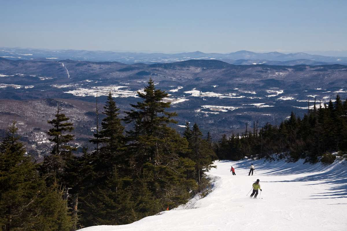 A ski trail drops off into the distance with scenic mountains and hills on the background.