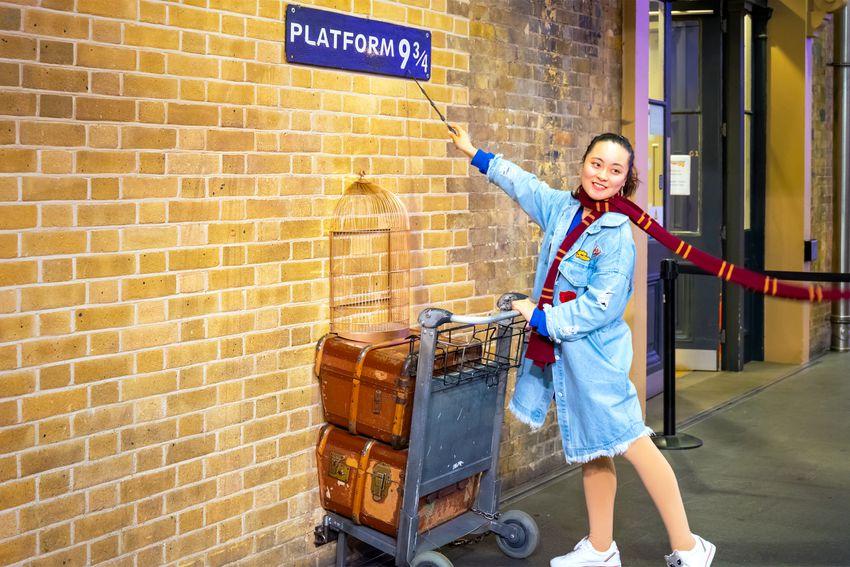 woman at platform 9 3/4 at king's cross station
