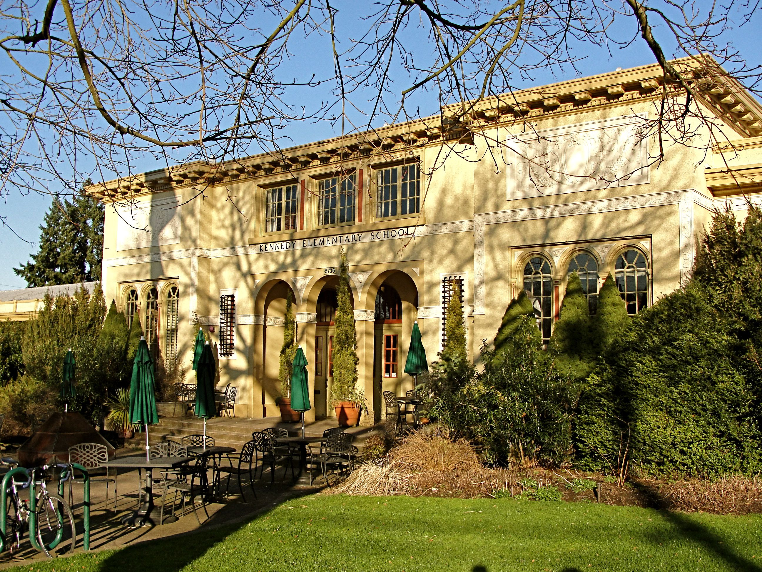 Exterior of the McMenamins Kennedy School with green umbrellas out front