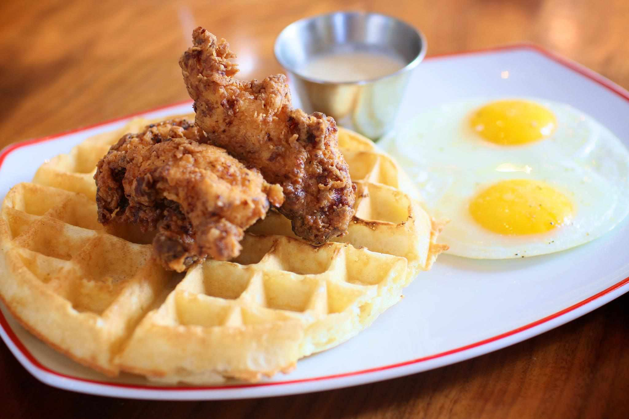 Two sunny side-up eggs and a small waffle with two pieces of chicken on a plate