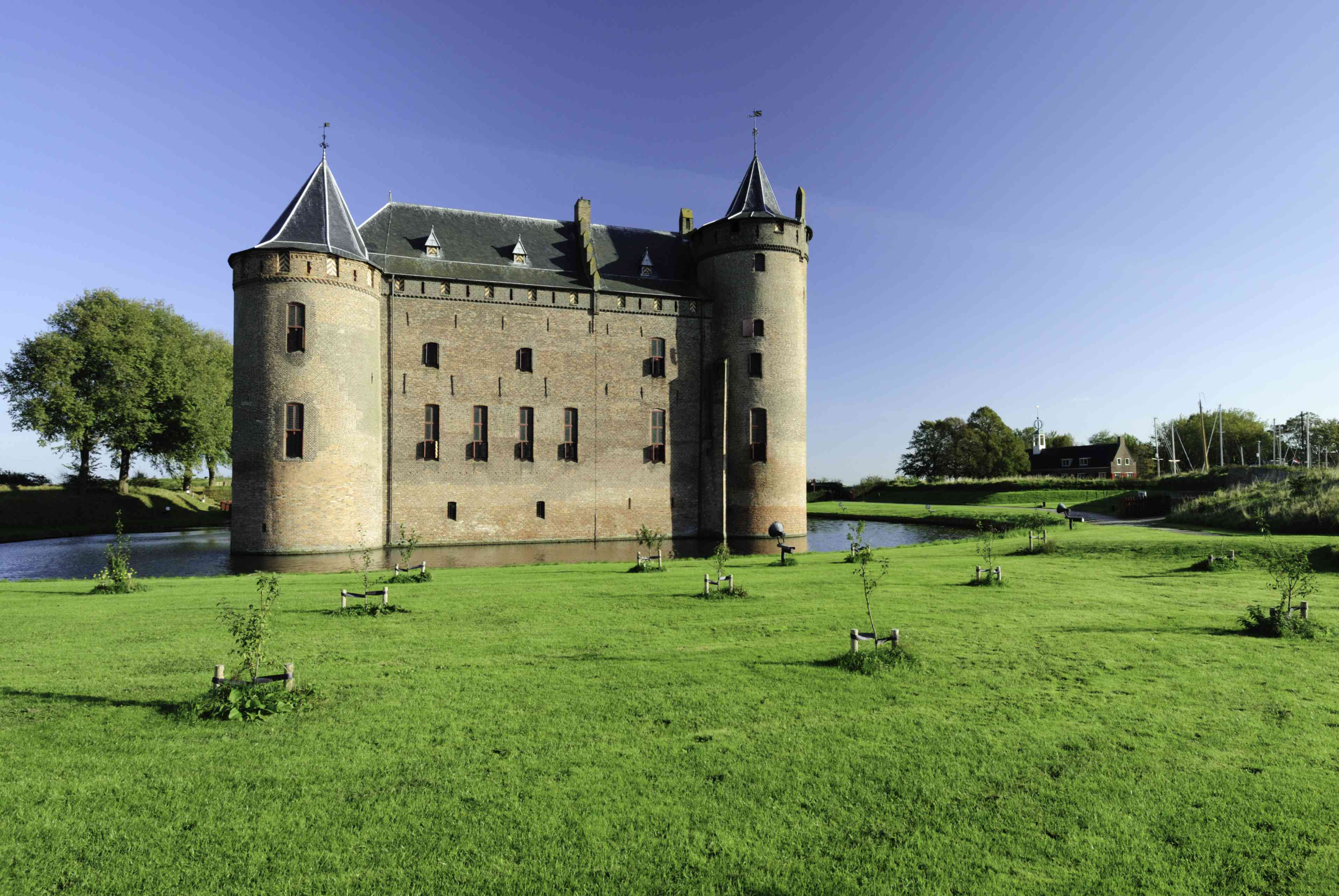 Medieval castle Muiderslot with a very green lawn around a moat.