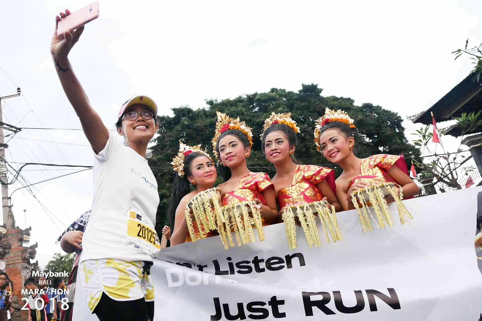 Marathon runner selfie-ing with Balinese dancers