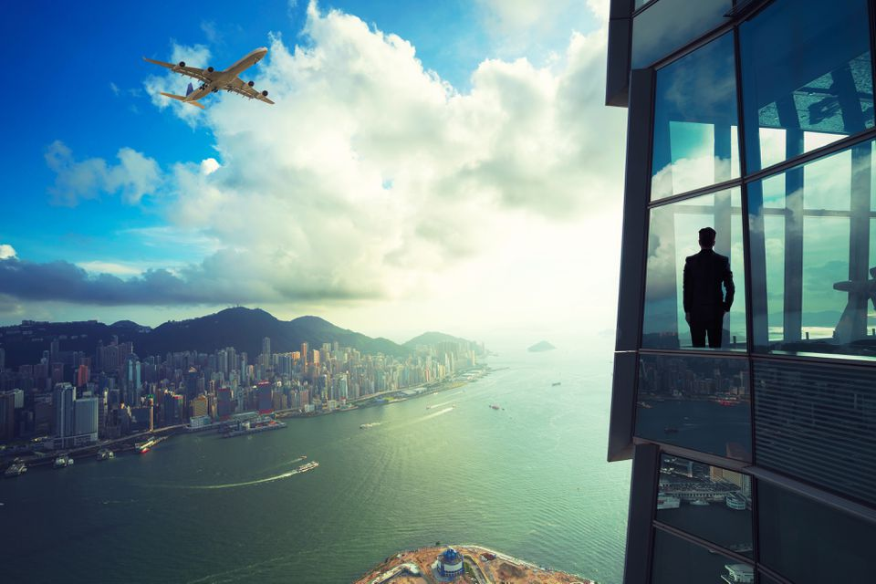 Businessman standing in modern room office with looking at Hong Kong cityscape