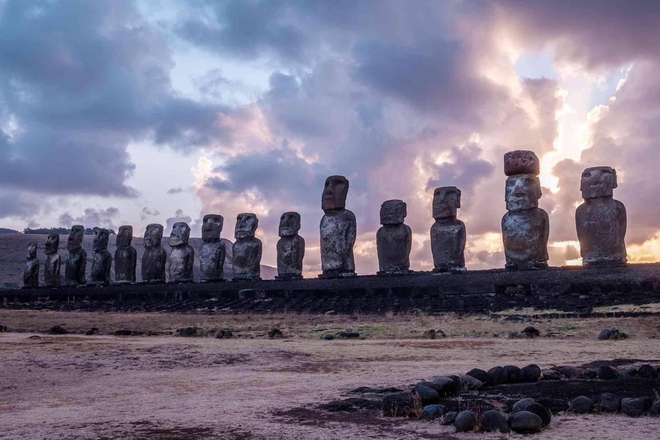 Moai statues against a cloudy sky at sunrise.