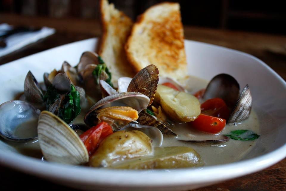 Steamed clams in a bowl with lemongrass-infused coconut milk, fingerling potatoes, cherry tomatoes and cilantro. There are two half-pieces of toast on the side of the bowl
