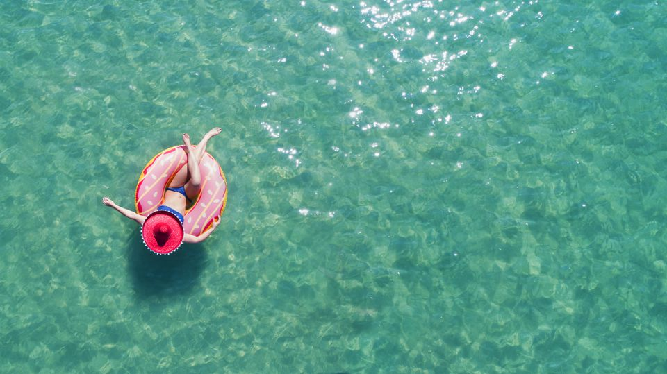 Lady floating in the sea in a rubber ring, wearing large hat