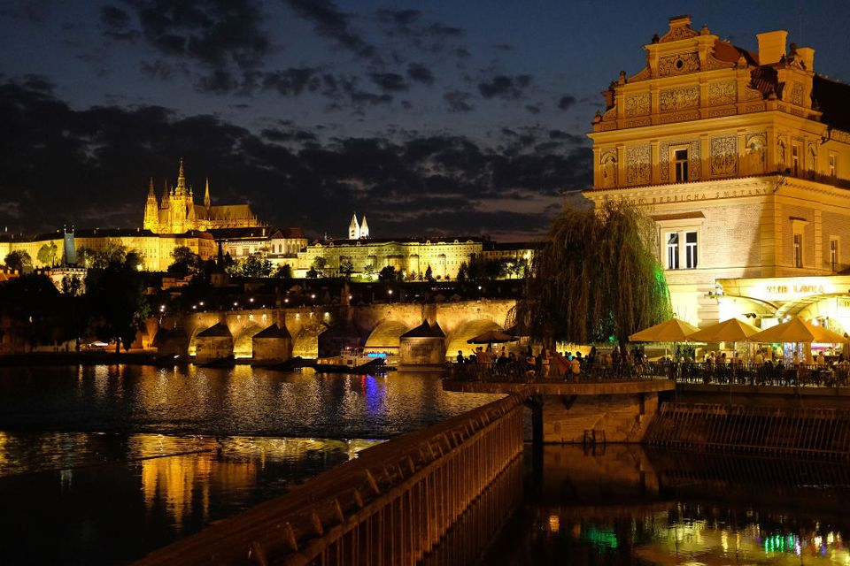 Prague Castle (L) and the Charles Bridge stand illuminated over the Vltava River