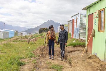 African couple walking through a township - stock photo