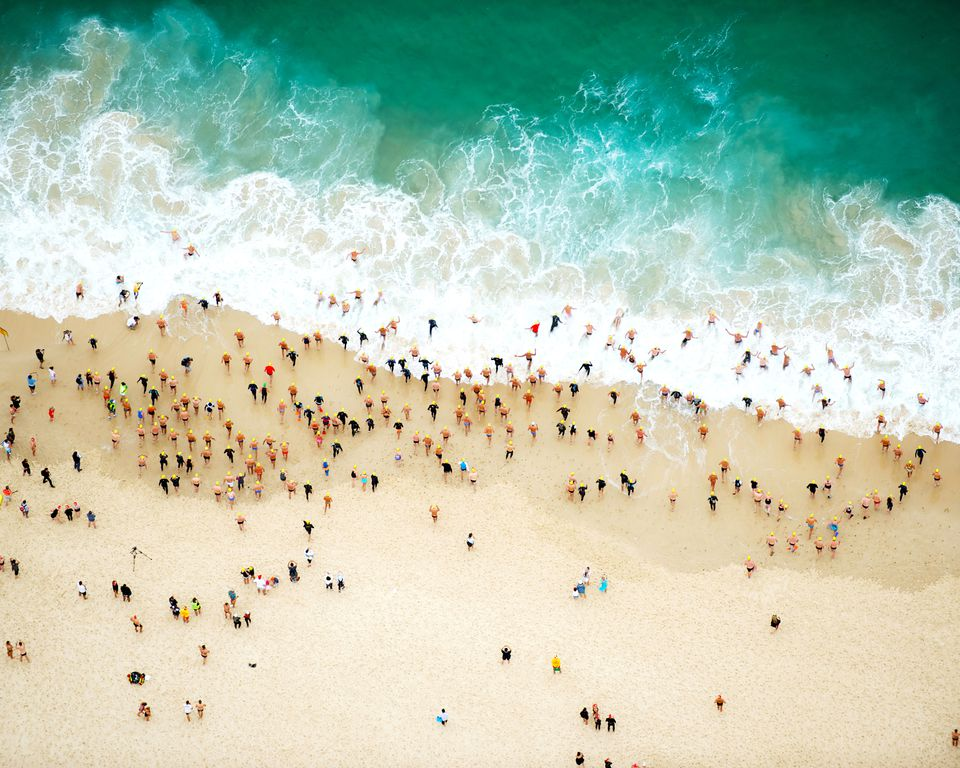 overhead view of people on a beach and in the ocean