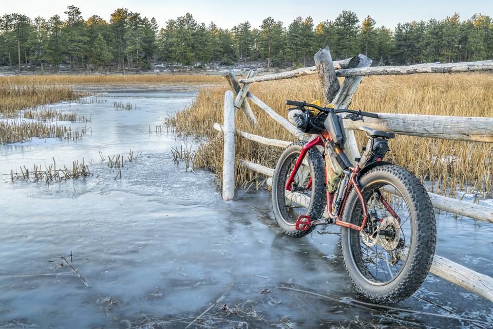a fat bike on icy stream leaning against a wooden fence