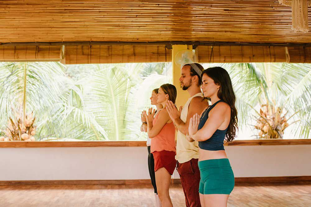 three women and one man standing in a line doing anjali mudra post in a Bali yoga studio