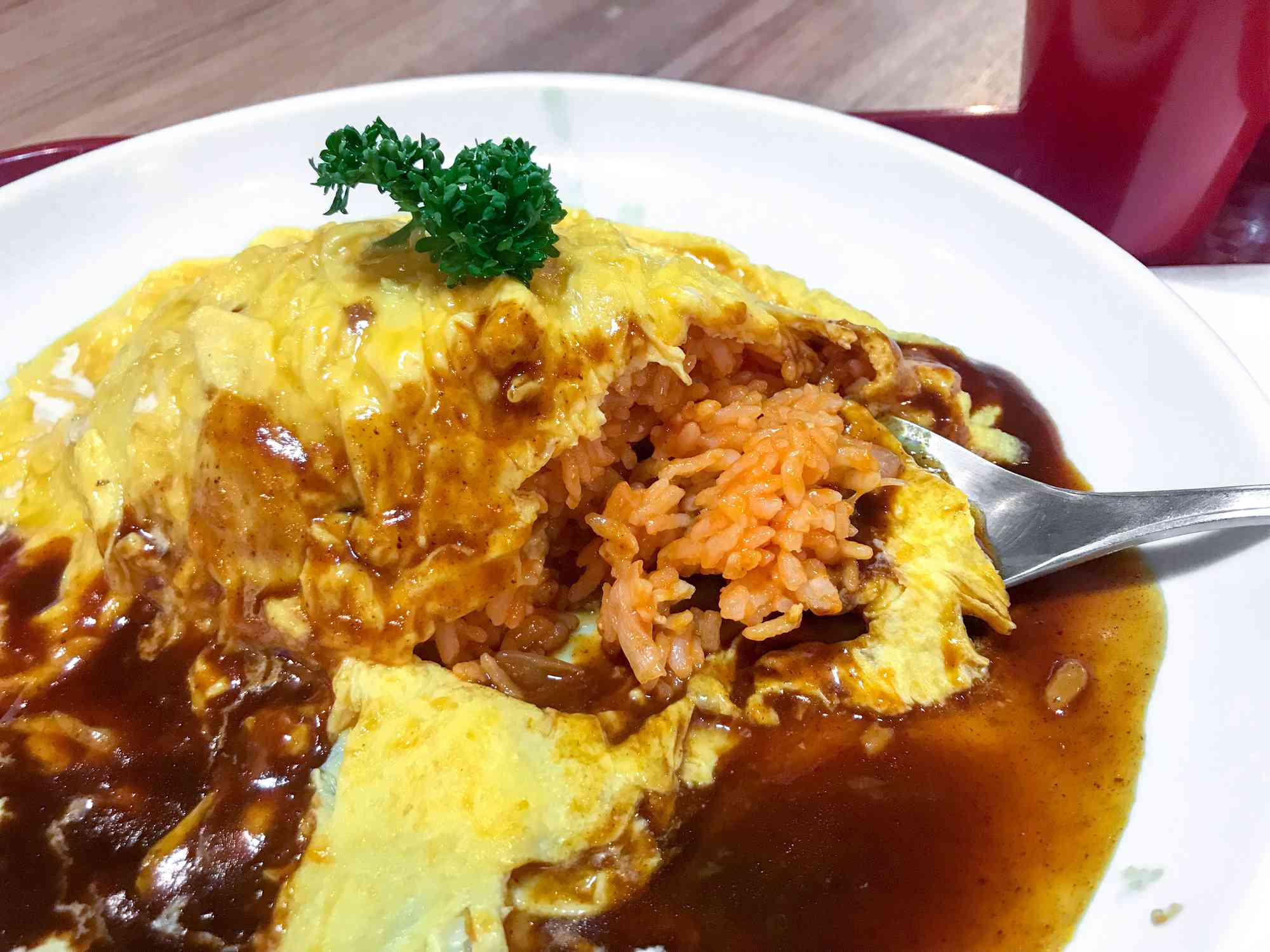 omurice with a bite taken out revealing the rice beneath the egg